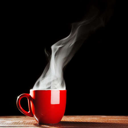 Steaming coffee cup on dark background photo