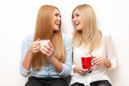 Two female friends drinking coffee and chatting photo
