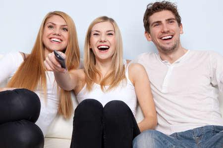 people watching tv: Grupo de j�venes que ven la TV en el hogar