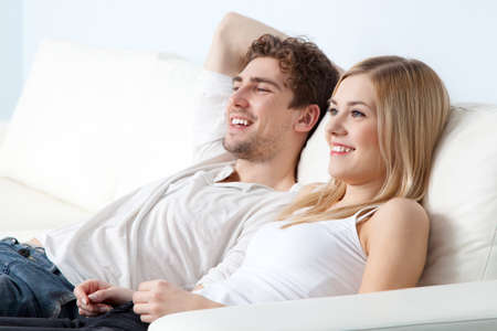 Young beautiful couple on a sofa at home photo