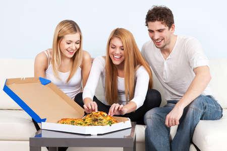 food woman: Groupe de jeunes gens mangeant de la pizza � la maison Banque d'images
