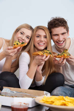 pizzas: Group of young people eating pizza at home