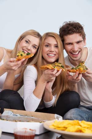 caja de pizza: Grupo de j�venes comiendo pizza en casa