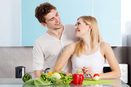 Young beautiful couple cooking at home photo