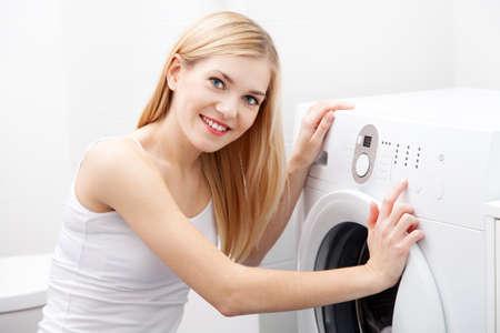 doing chores: Young beautiful woman using a washing machine