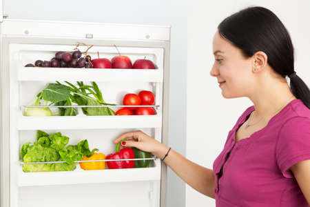 Young woman looking into a refrigerator photo