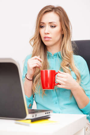 Young blond woman working with a laptop Stock Photo - 24963138