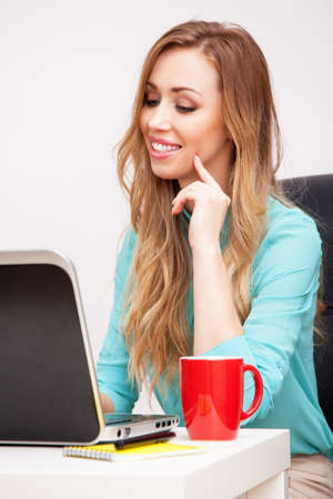 Young blond woman working with a laptop photo