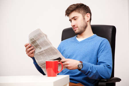 Young man reading a newspaper photo