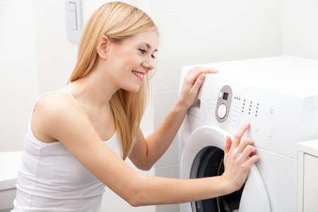 daily room: Young beautiful woman using a washing machine