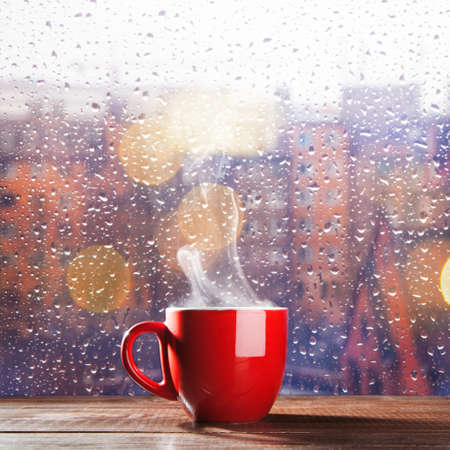 Steaming cup of coffee over a cityscape background Imagens