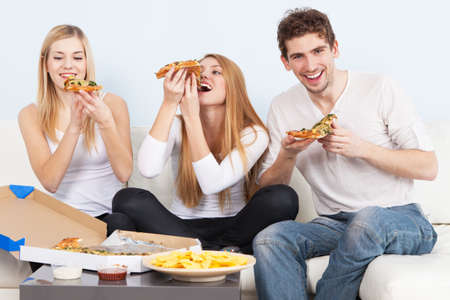 eating pizza: Group of young people eating pizza at home