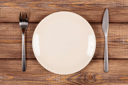 wooden plate: Empty plate on a wooden table Stock Photo