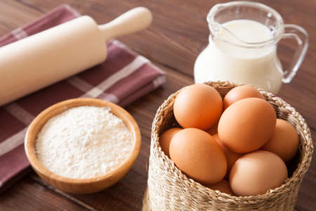 Eggs, milk and flour on a wooden table photo