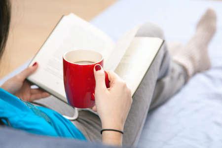 mujer en la cama: Mujer que lee un libro en la cama