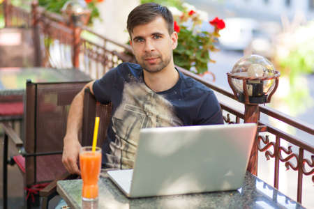 Young businessman working with a laptop in a cafe photo