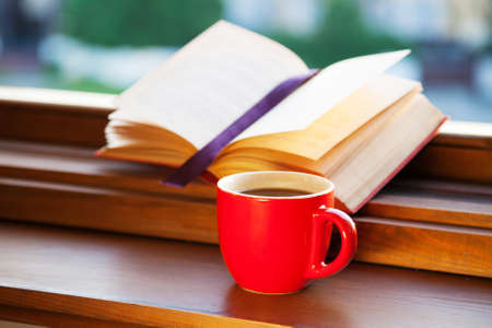 Books and a coffee cup on a windowsill photo