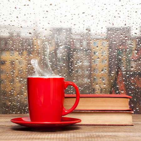 Steaming coffee cup on a rainy day window background photo