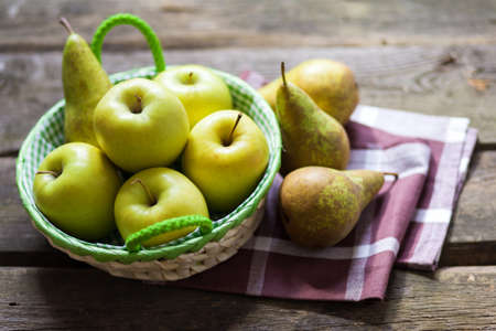 Fresh green apples and pears on a wooden table photo