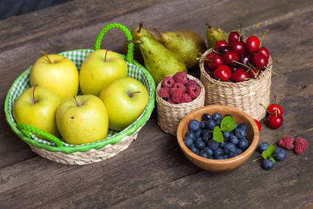 Fresh juicy apples, pears and berries on a wooden table photo