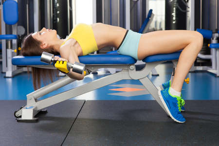 cross bar: Young slim woman exercising in a gym