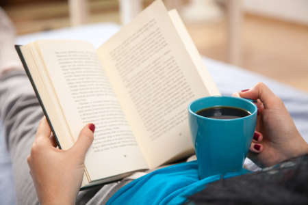 Woman reading a book and drinking coffee