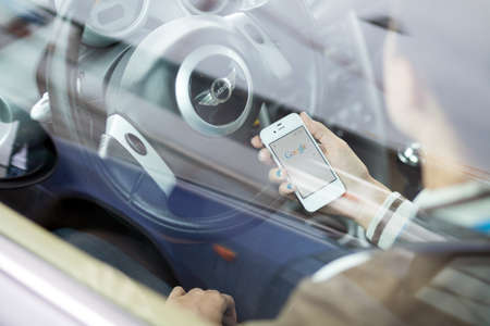 WROCLAW, POLAND - AUGUST 05, 2014: Photo of a young woman sitting in a Mini Cooper car holding an iPhone 4 smartphone device with a Google search app running