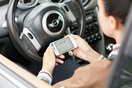 cooper: WROCLAW, POLAND - AUGUST 05, 2014: Photo of a young woman sitting in a Mini Cooper car holding an iPhone 4 smartphone device with a Google search app running