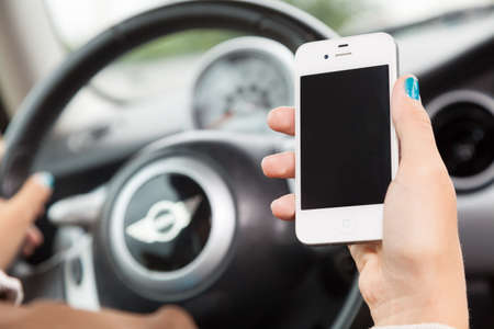 WROCLAW, POLAND - AUGUST 05, 2014: Photo of a young woman sitting in a Mini Cooper car holding an iPhone 4 smartphone device