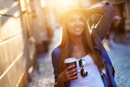 go shopping: Young stylish woman drinking coffee to go in a city street Stock Photo