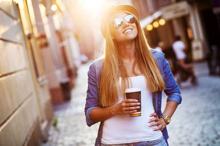 mujer tomando cafe: Elegante Joven beber café para ir en una calle de la ciudad Foto de archivo