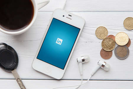 media gadget: WROCLAW, POLAND - JULY 31, 2014: Photo of iPhone 4 smartphone device with Linkedin app running - a social network for professionals Editorial
