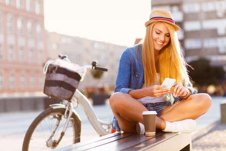 telefonok: Fiatal, elegáns nő egy bicikli egy városi utca