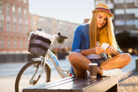 都市通りで自転車を持つ若いスタイリッシュな女性