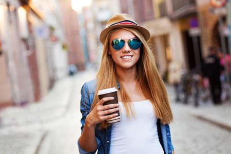 若いスタイリッシュな女性コーヒーを飲みに街に行く