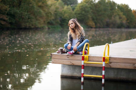 Young beautiful girl sitting on a pier photo