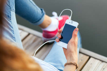 girl headphones: WROCLAW, POLAND - OCTOBER 12, 2014: Teenager sitting on a pier holding a smartphone Stock Photo