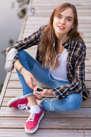 Young beautiful girl sitting on a pier, listening to music from her smartphone photo