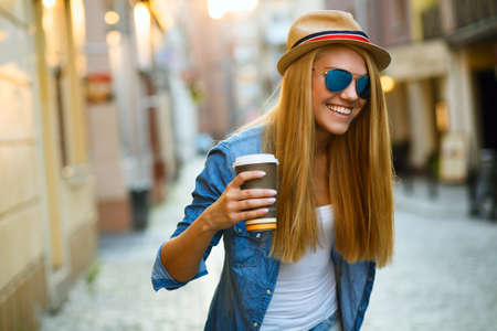 Young stylish woman drinking coffee to go in a city street Banque d'images