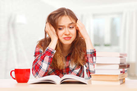 textbooks: Young girl stressed over her textbooks