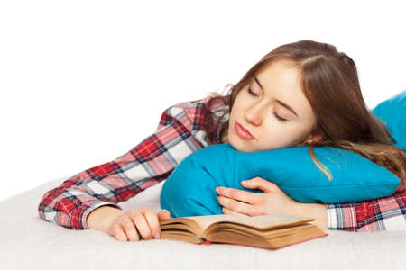 Young girl slepping with a book in bed.