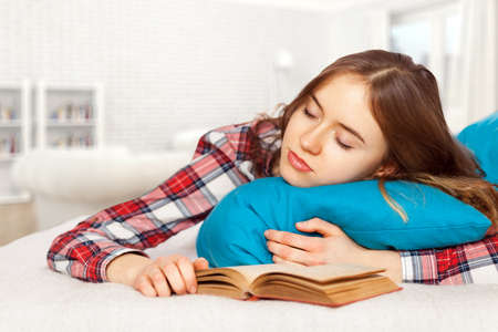 Young girl slepping with a book in bed. photo