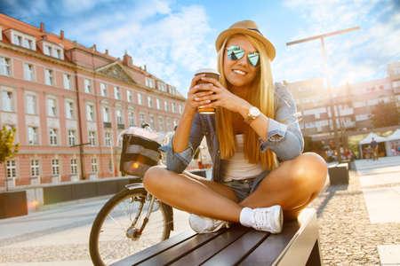 街の通りで自転車を持つ若いスタイリッシュな女性。 写真素材