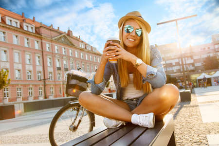 Young stylish woman with a bicycle in a city street. Stock Photo