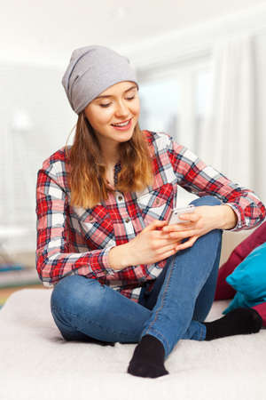 teen girl: Teenage girl in a checked shirt with a smartphone