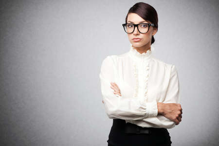 Strict woman in large glasses, isolated on white background photo