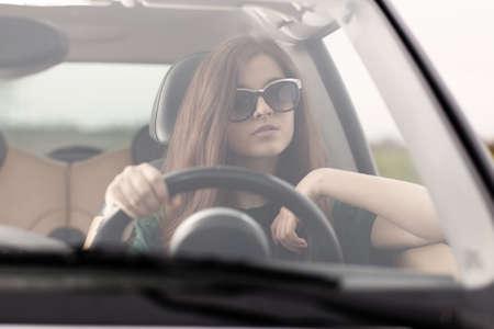 Young beuatiful woman driving a car. photo