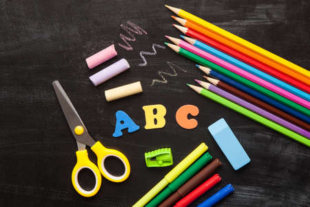 office accessories: School and office accessories on blackboard surface