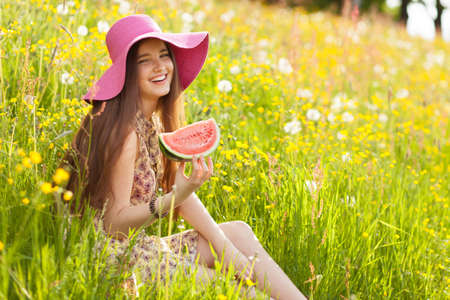 melon field: Young beautiful woman eating a watermelon.