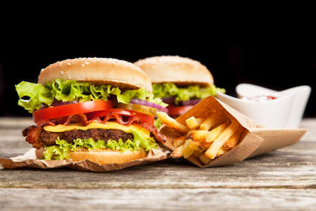 Delicious hamburger and fries on black background